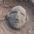 Sculpture of a human face by sand beach — Stock Photo