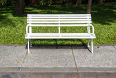 White bench in lush garden or park — Stock Photo