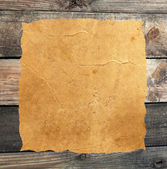 Empty grunge paper against wood background — Stock Photo