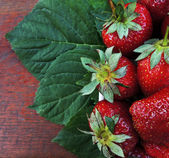 Fresh strawberry with leaf on wooden table — Stock Photo