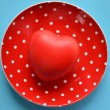 Heart on red plate of polka dots on blue background — Stock Photo
