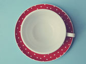 Red cup of polka dots on blue background vintage — Stock Photo