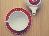 Red polka dot kettle and cup on wooden vintage — Stock Photo