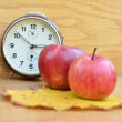Red apples and clock on wooden table — Stock Photo