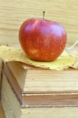 Fresh red apple on old books — Stock Photo