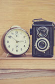 Old camera and brown clock on books — ストック写真