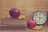 Old brown clock with apples and books — Stock Photo