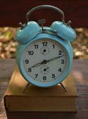 Retro turquoise clock on book — Stock Photo