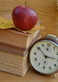 Vintage books with old clock and red apple — Stock Photo