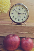 Vintage books with clock and apples — Stockfoto