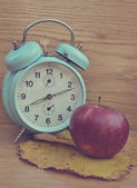 Vintage turquoise clock and apple — Stock Photo