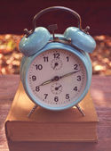 Retro turquoise clock on book — Stockfoto