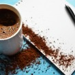 Cup of black coffee on blue background and blank paper — Stock Photo