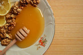 Honey with walnuts and lemon on wooden background — 图库照片