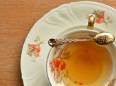 Cup of tea and teaspoon on wooden — Stock Photo