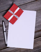 Blank paper with gift on wooden background — Stock Photo