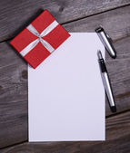 Blank paper with gift on wooden — Photo