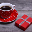 Cup of coffee and gifts at background — Stock Photo