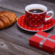 Red cup of coffee and croissant and small gift — Stock Photo