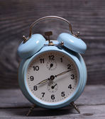 Retro turquoise clock on wooden background — Stock Photo