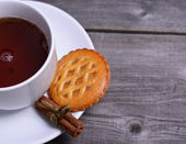 Cookies with cinnamon and cup of tea on wooden background — Stock Photo