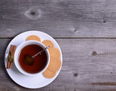 Cookies and cup of tea on wooden — Stock Photo