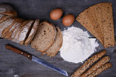 Fresh bread, eggs and flax chips on the wooden — Stock Photo