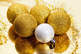Gold christmas balls and tinsel with reflection — Stock Photo