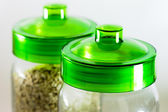 Glass kitchen pots with green caps — Stock Photo