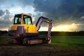 Excavator standing on a construction site — Stock Photo