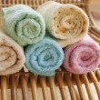 Multicolour towels rolls on wood chair — Stock Photo