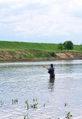 Pêcheur avec rotation dans des vêtements spéciaux. — Photo