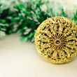 Christmas background with gold carved ball and green tinsel on white. — Stock Photo #31361875