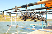 Reels with rods on a special stand with bite alarms on the jetty on a sunny day. — Zdjęcie stockowe
