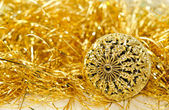 Christmas background with gold carved ball and gold tinsel on white — Stock Photo