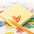 Small note pad and a pencil on a background of multi-colored paper clips on white. — Stock Photo