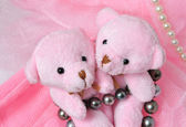 Two amusing pink teddy bear on a pink background with pearls. — Stock Photo