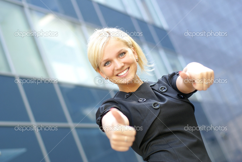 Young pretty business woman shows the sign of success over modern background          — Stock Photo #14913245