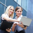 Two young attractive business women looking to the laptop - Foto de Stock