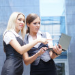 Two young attractive business women looking to the laptop — Stock Photo #14928575