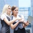 Two attractive business women over modern street background - Foto de Stock
