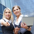 Two young attractive business women looking to the laptop — Stock Photo