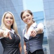 Two young attractive business women demonstrate the success — Stock Photo