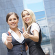 Two young attractive business women demonstrate the success — Stock Photo #14928681