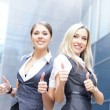 Stock Photo: Two attractive business women over modern street background