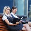 Two attractive business women over modern street background — Stockfoto