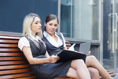Two attractive business women over modern street background — Stock Photo