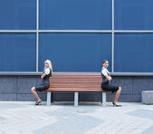 Quarrel between two business women sitting on the bench — Stock Photo