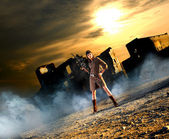 Young and sexy woman with the machine gun in apocalyptic landscape — Stock Photo