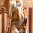 Body of young beautiful woman in lingerie standing over vintage background — Stock Photo #14934265
